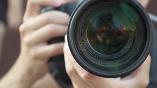 junger Mann mit einer professionellen Kamera, um Fotos und Videos zu machen. Großes Zoomobjektiv