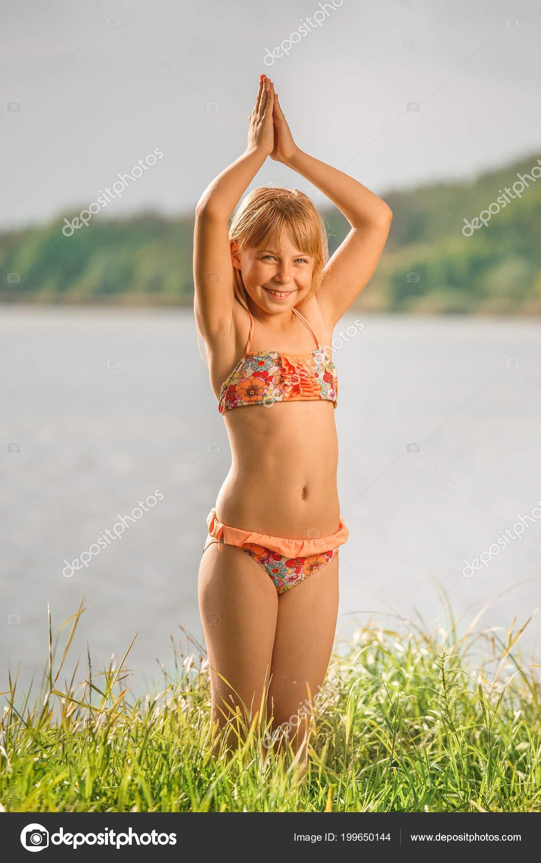 dcf767660 Niña con pie de pelo en un traje de baño en el verano contra una chica de  river.a en un traje de baño de color rojo anaranjado brillante — Foto de ...