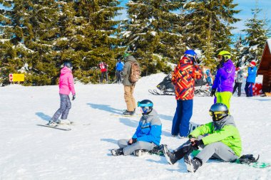 several skiers rest on the top of the mountain. A group of people in ski suits sitting on the snow s makes a selfie.