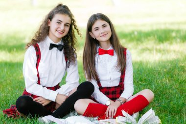 two schoolgirls in red school uniforms sit on a green lawn with books.girlfriends or sisters teach outdoor lessons