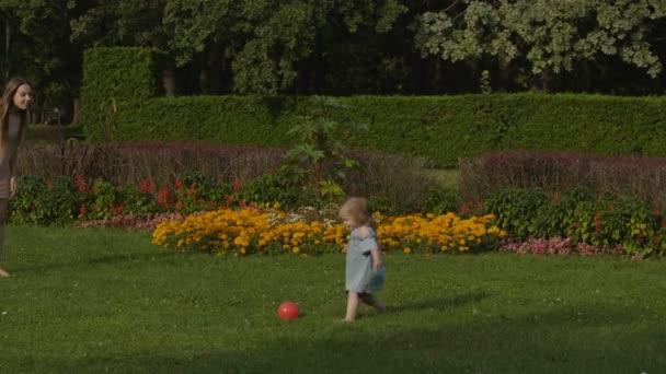 Kislány, anya játszó piros labda, zöld fű a nyáron könnyű parkban. Baba szórakozni. Színes nyári virágok háttér. Boldog családi koncepció.