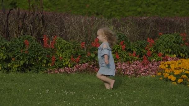 Pomalý pohyb baby Girl běh pryč na zelené trávě v létě světlo v parku. Děťátko se bavit. Barevné letní květiny pozadí. Šťastný rodinný koncept.