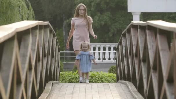 Slow motion baby with mom are running on a wooden bridge in the sunset light. Backlight sunset light. Happy family concept. Woman with long hair.
