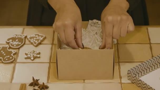 Közeli kép a nő előkészíti egy doboz mézeskalács cookie-kat egy karácsonyi ajándék. Karácsonyi ajándék. Hagyományos házi készítésű karácsonyi desszert.