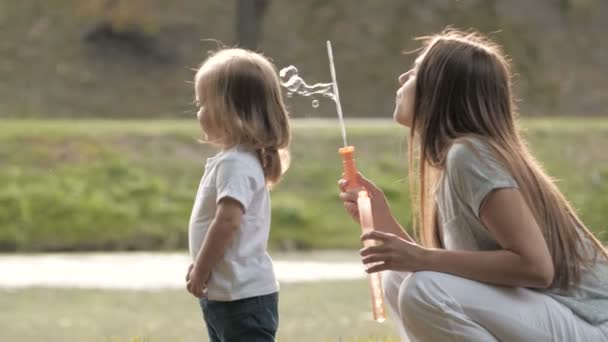 Baby girl with mother make soap bubbles in the summer park in sunset light.