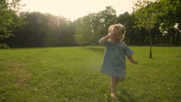 Baby girl running through the grass in garden in sunset sunlight. Slow motion. Happy smiling baby girl.