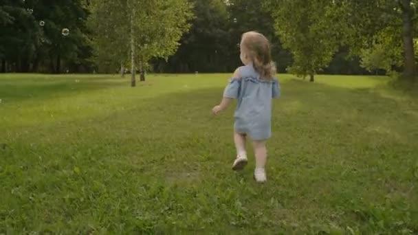 Holčička, která prochází trávou a chytá mýdlové bubliny v zahradě na slunci. Zpomaleně. Šťastná usměvavá holčička.