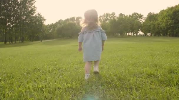 Holčička, která prochází trávou v zahradě v slunci. Zpomaleně. Šťastná usměvavá holčička.
