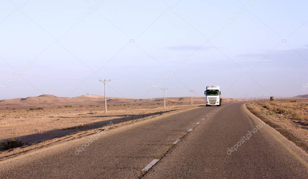 Truck goes to highway through desert of Jordan, power poles along asphalt road in valley, early morning in wilderness after sunrise.