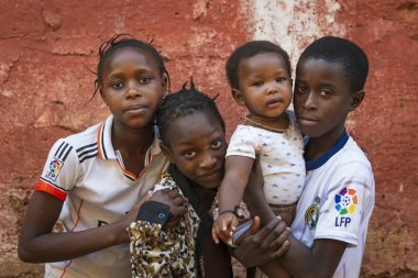 Bissau, Republic of Guinea-Bissau - January 31, 2018: Group of children outside their home at the Cupelon de Cima neighborhood in the city of Bissau, Guinea Bissau. stock vector