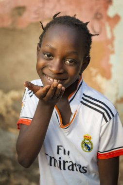 Bissau, Republic of Guinea-Bissau - January 31, 2018: Portrait of a smiling young girl at the Cupelon de Cima neighborhood in the city of Bissau, Guinea Bissau stock vector