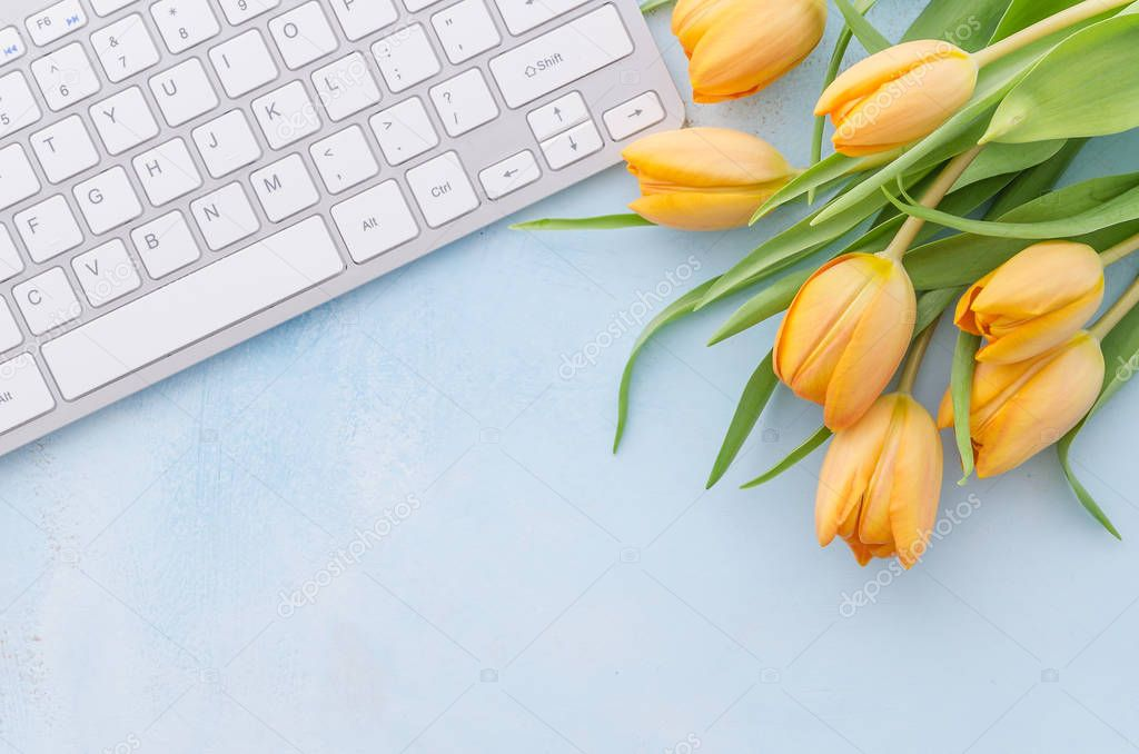 Laptop keyboard and yellow tulips over light blue background. Spring summer decorated blossom, desktop , flat lay top view copy space