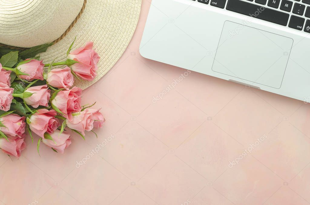 Womens workplace flat lay with pink roses on a pink background with a laptop and a straw hat. Copy space top view
