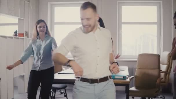 Young Caucasian male executive doing a funny victory dance at fun casual office party, celebrate business achievement 4K