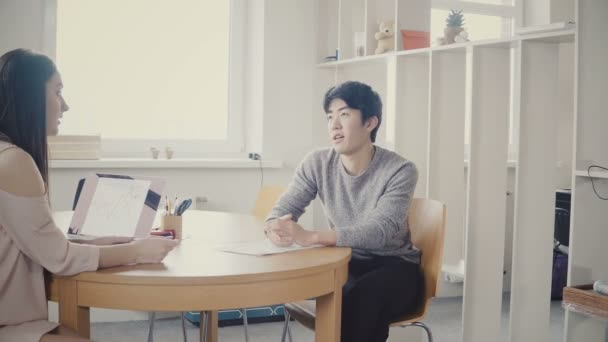 Young Asian man talking to attractive HR woman at job interview. Diverse business people cooperate in modern office 4K.