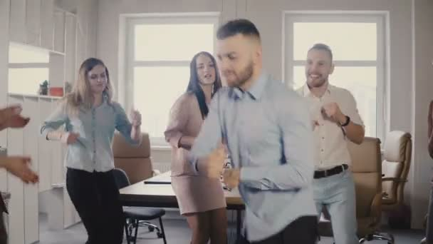 Young European businessman dancing together with colleagues at fun casual office party, celebrating career promotion 4K.