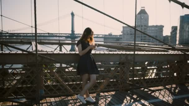 Beautiful Caucasian woman stands using smartphone messenger app at Brooklyn Bridge, New York amazing skyline panorama 4K
