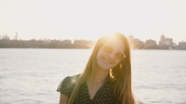 Portrait of happy relaxed Caucasian girl in sunglasses posing, smiling at camera on amazing city skyline beach sunset 4K