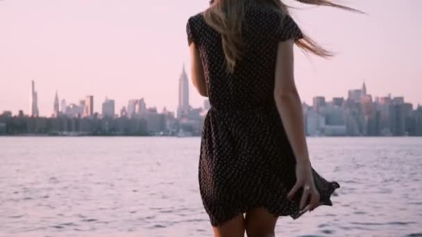 Beautiful girl in sunglasses walks down by camera to sit by the water, watching New York scenery on sunset slow motion.