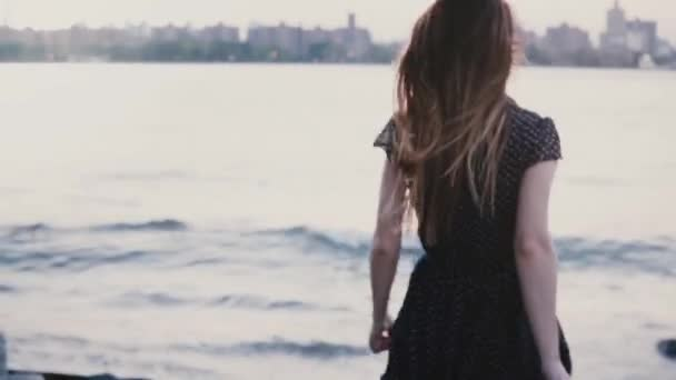 Camera follows girl in black dress run down to big river shore, watch amazing New York sunset scenery slow motion. Young excited female tourist enjoying beautiful cityscape view. Best moments of life.