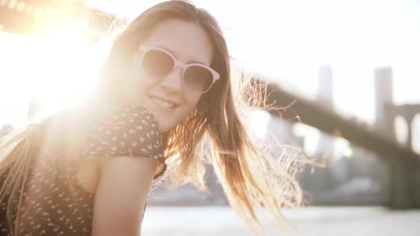 Slow motion close-up of happy European female tourist in sunglasses smiling at camera at sunset New York scenery.