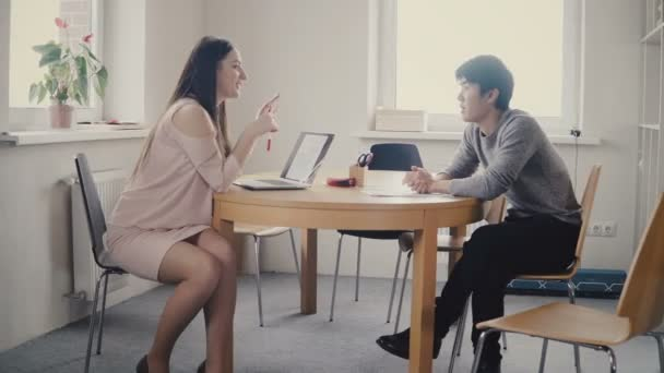 Atraktivní šťastné ženské vůdce poslech asijské mužský kolega. Smíšené etnického původu firmy pracují v kanceláři loft 4k