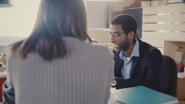 zwei nervöse afrikanisch-amerikanische Manager sitzen am Tisch, hören einer nicht wiedererkennbaren Anwältin beim Bürogespräch zu 4k.