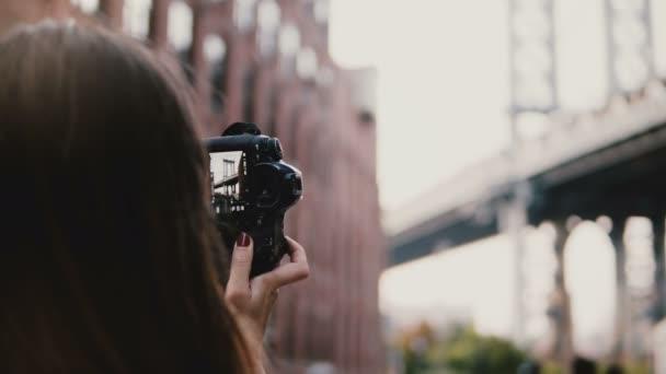 rückseite unkenntliche frau mit kamera macht fotos von brooklyn bridge at dumbo district in new york city 4k.