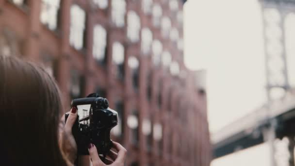 rückseite professionelle fotografin mit kamera macht bilder von brooklyn bridge at dumbo district, new york 4k.