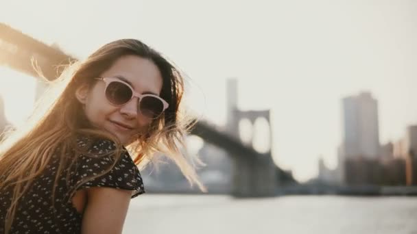 Happy European girl in sunglasses smiling, enjoying amazing river sunset at Brooklyn Bridge New York, looking at camera.