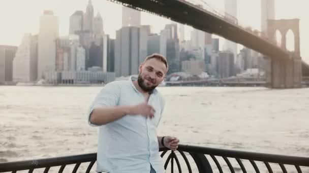 Boldog sikeres kaukázusi Férfi mosolyogva kamera, bemutató gesztusok, mutatva csodálatos New York-i városi táj mögött 4k