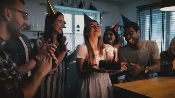 Happy European girl holding birthday cake, making a wish and blowing, multiethnic friends sing at fun party slow motion.