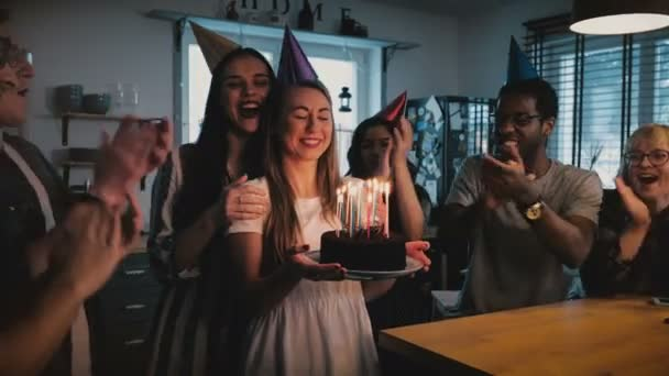 Happy Caucasian girl holding birthday cake, making a wish at cheerful fun multiethnic party with friends slow motion 4K. Young millennial mixed race group celebrating together in fun hats at home.
