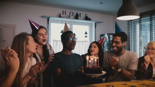 Šťastný afroamerické mladý muž, který držel narozeninový dort se svíčkami, slaví s mnohonárodnostní přátel zpomalené přehrávání 4k