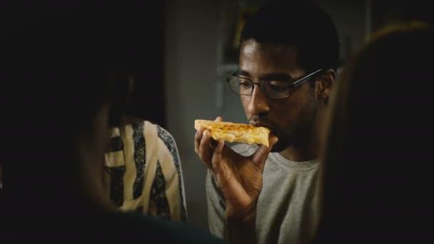 Američan Afričana mladého muže jíst pizzu na neformální party house. Mladí lidé mají rychlé občerstvení v kuchyni doma