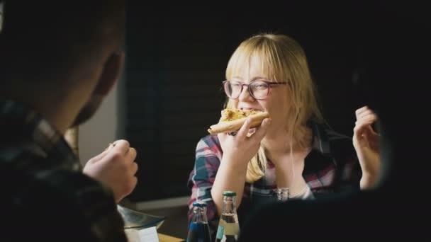 Krásná mladá Evropská dívka v brýlích se těší jíst pizzu a mluví na neformální večírek s přáteli