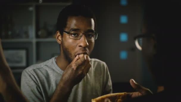 Africké americké neformální mladý muž v brýlích, jíst pizzu na večírku. Happy přátelé vychutnat rychlé občerstvení v kuchyni doma