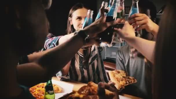 Posouvání záběr mladých šťastný, že mnohonárodnostní přátelé dělat toast, jíst pizzu a usmívá se na zábavu příležitostné house strana