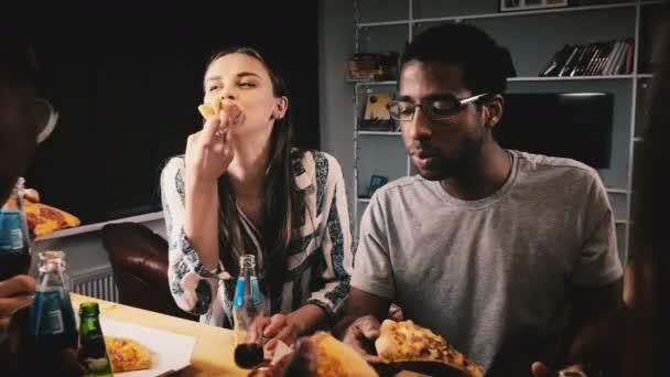 Smíšený etnické skupina happy mladých přátel, jíst pizzu a popíjejí u příležitostné house party v kuchyni stůl