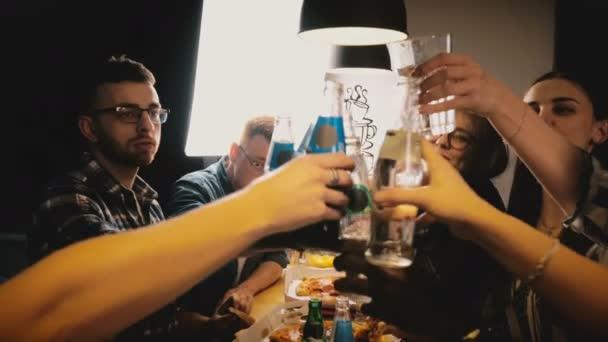 Happy mladí mnohonárodnostní přátelé slaví, jíst pizzu a popíjejí na neformální party v kuchyni stůl Zpomalený pohyb