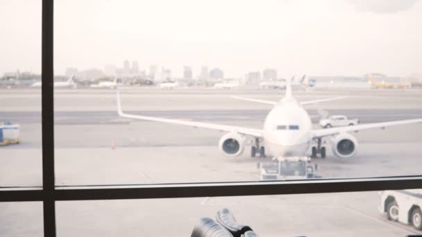 Unrecognizable female traveler with bag walks up to airport lounge terminal window to enjoy the view of airplanes.
