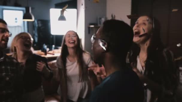 Happy mnohonárodnostní mladí lidé tančící pohromadě, oslavující přátelství v fun narozenin s konfety Zpomalený pohyb