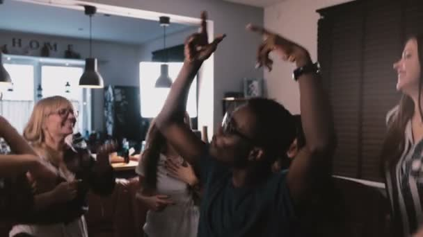 Successful African American freelance worker celebrating victory with multiethnic colleagues at house party slow motion.