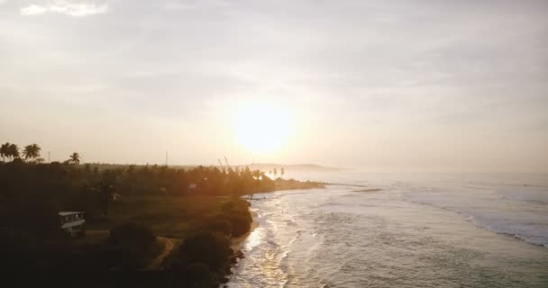 Drone flying forward along breathtaking tropical sunset beach, white foaming ocean waves breaking at amazing coast line.