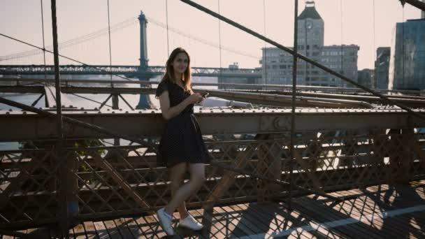 Young pretty European girl looking around, using smartphone app at Brooklyn Bridge, New York amazing riverside view 4K.