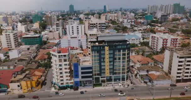 Drone flying right over Colombo, Sri Lanka. Aerial view of cityscape with buildings, street traffic and small railroad.