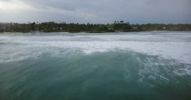Drone flying backwards above breathtaking sea waves with white foam near beautiful exotic coastline with tropical trees.