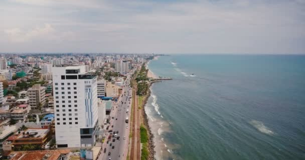 Drone flying over beautiful coastline of Colombo, Sri Lanka. Amazing aerial view of busy city street and ocean waves.