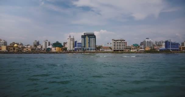 Drone flying low above the ocean water towards Colombo city coastline, Sri Lanka, modern buildings on the shore line.