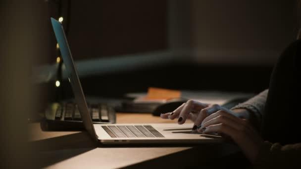 Közelkép nő dolgozik a laptop éjjel. Női kezek segítségével notebook touchbar és a nyom. Munkamániás. 4k.